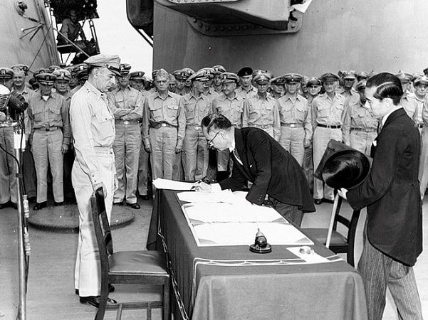 Photo: Japanese Foreign Affairs Minister Mamoru Shigemitsu signs the Japanese Instrument of Surrender aboard the USS Missouri as General Richard K. Sutherland watches, 2 September 1945. Credit: Army Signal Corps; Wikimedia Commons.