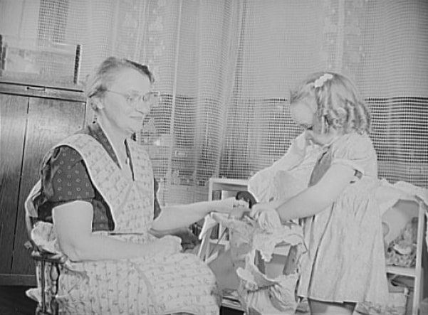 """Photo: Like any other grandmother, skilled worker Eva Smuda enjoys the """"children's hour"""" each day, and her work never leaves her too tired for those games of make-believe with five-year-old Barbara, 1942. Credit: Library of Congress, Prints and Photographs Division."""