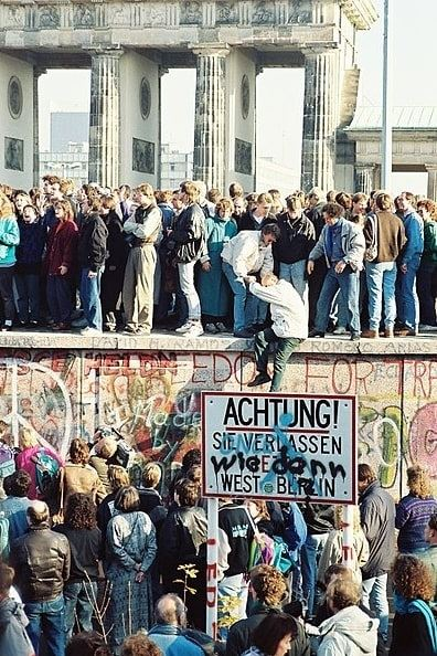 """Photo: people atop the Berlin Wall near the Brandenburg Gate on 9 November 1989. The text on the sign """"Achtung! Sie verlassen jetzt West-Berlin"""" (""""Notice! You are now leaving West Berlin"""") has been modified with an additional text """"Wie denn?"""" (""""How?"""")"""