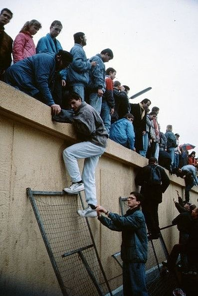 Photo: people climbing on top of the Berlin Wall, November 1989