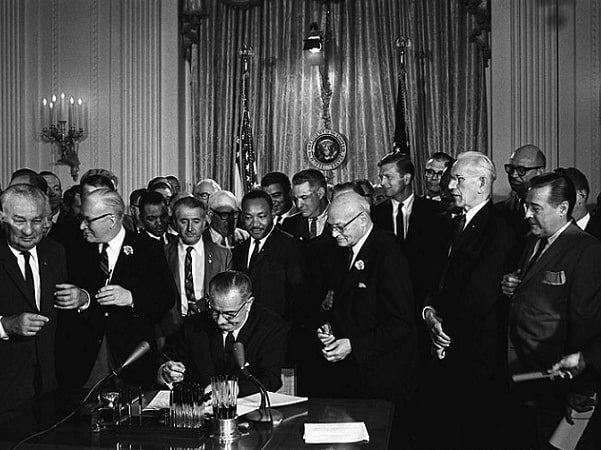 President Lyndon B. Johnson signs the Civil Rights Act on 2 July 1964. Among the guests behind him is Martin Luther King Jr. Credit: White House Press Office; Cecil Stoughton; Wikimedia Commons.