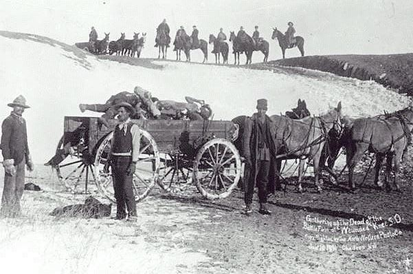 Photo: civilian burial party, loading Lakota victims of the Wounded Knee Massacre onto a cart for burial. Credit: Charles C. Pierce; Wikimedia Commons.