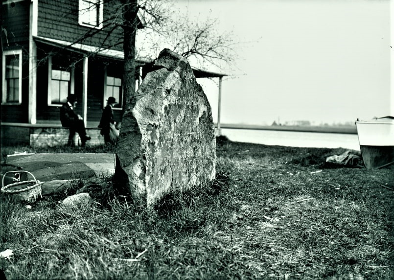"""Photo: two people gaze at the Parker River behind the memorial stone erected in 1902 for the Newbury, Massachusetts, settlement. The inscription on the stone reads """"Landing Place of the First Settlers 1635."""""""