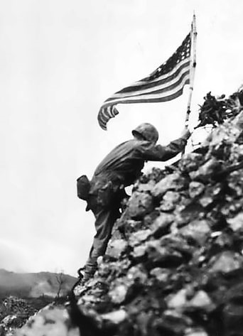 Photo: Lt. Col. Richard P. Ross Jr., commander of 3rd Battalion, 1st Marines, braves sniper fire to place the United States' colors over the parapets of Shuri Castle during the Battle of Okinawa on 29 May 1945