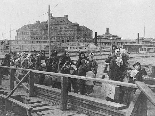 Photo: immigrants coming up the board-walk from the barge, which has taken them off the steamship company's docks, and transported them to Ellis Island, 1902. Credit: Library of Congress, Prints and Photographs Division.