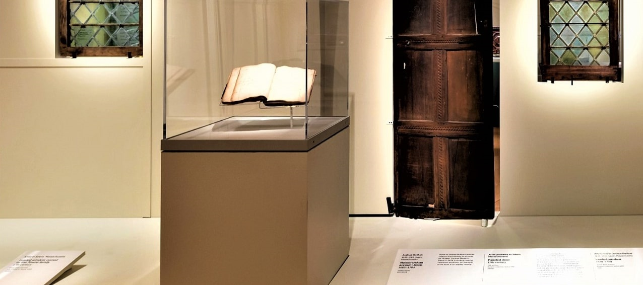 Photo: a display of Joshua Buffum's account book in a glass case. Also in the photo, a 17th century paneled door and leaded windows. Credit: Peabody Essex Museum.