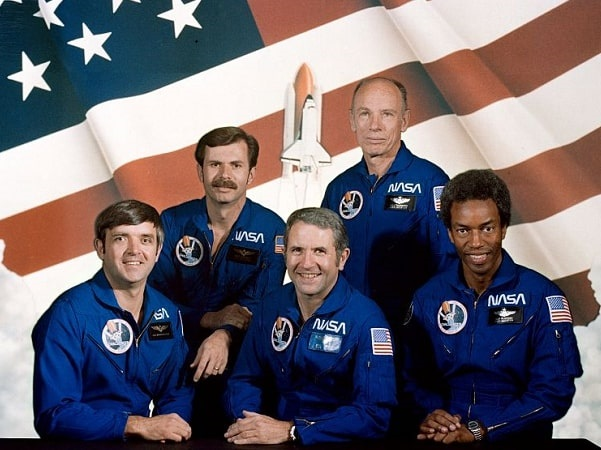 Photo: official STS-8 crew portrait in flight suits. Seated from left to right are Daniel C. Brandenstein, pilot; Richard H. Truly, commander; and Guion S. Bluford Jr., mission specialist. Standing from left to right are Dale A. Gardner, mission specialist; and William E. Thornton, mission specialist. Credit: NASA; Wikimedia Commons.