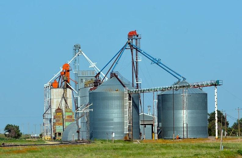 "Photo: Nebraska grain bins and elevator. Credit: ""Nebraska grain silo RAAM 2015 by D Ramey Logan.jpg from Wikimedia Commons by D Ramey Logan, CC-BY 4.0."""