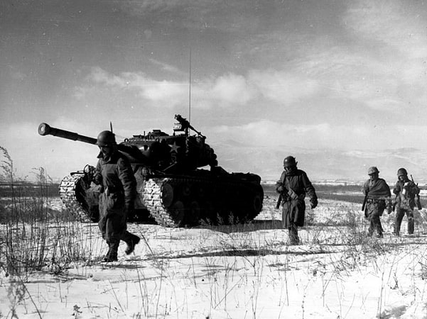 Photo: a column of the U.S. 1st Marine Division moves through Chinese lines during their breakout from the Chosin Reservoir during the Korean War, December 1950. Credit: Corporal Peter McDonald, USMC; Wikimedia Commons.